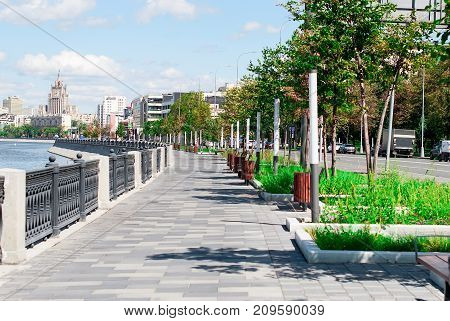 Trees along waterfront promenade with lanterns by the business city center at sammer day time. View of the embankment across the Moscow River and green lawn Moscow Russia