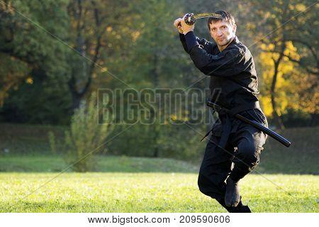 Ninja in black kimono is practicing martial arts with sword outdoors.