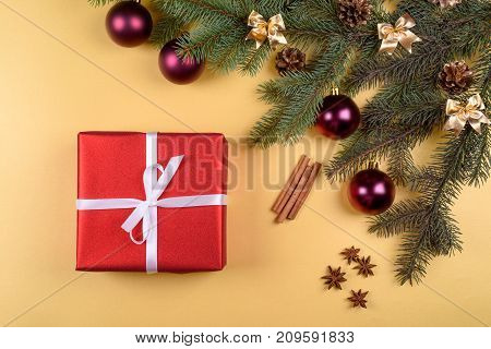 Christmas background with red gift box fir tree branches with glass balls pine cones cinnamon sticks and stars anise on golden background free space. Flat lay top view with copy space