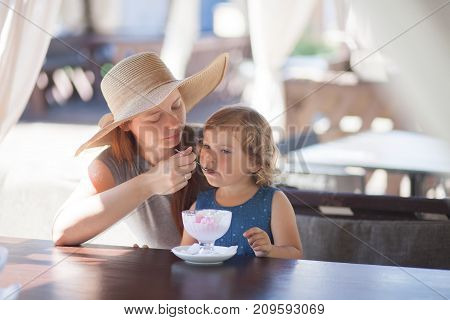 Mother feeding little girl with ice cream indoors. Family lifestyle.