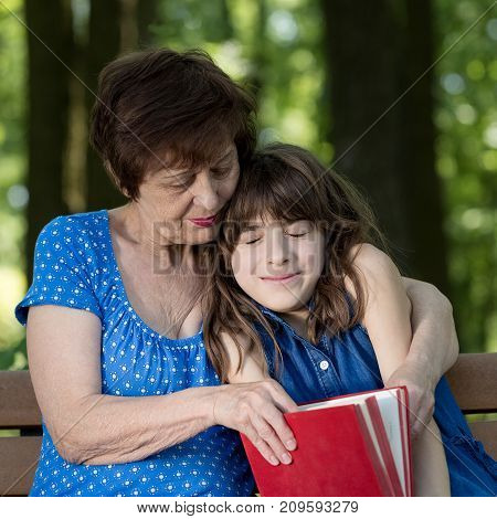 Elderly woman and girl are sitting on the bench embracing and reading a book against green nature background. Grandmother and granddaughter. Concept of harmony relationship between generations.