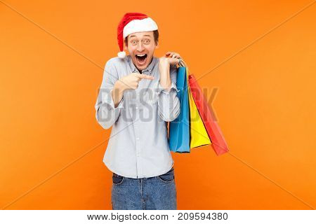Positive Happiness Man Looking At Camera And Toothy Smile. Shocked Man Holding Many Bags And Pointin