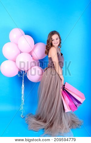 Young smiling woman in dress holding shopping bags near pink balloons over blue background in black friday holiday free space. Beauty fashion sale concept. Girl on blue background with copy space