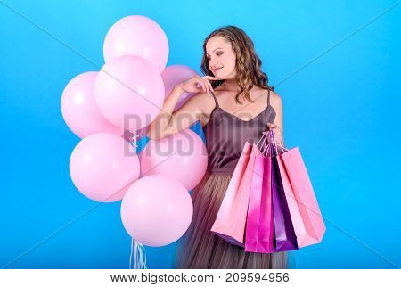 Beautiful young smiling woman in dress holding shopping bags and looking at pink balloons over blue background in black friday holiday free space. Beauty fashion seasonal sale concept