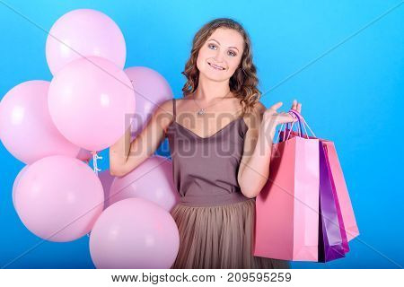 Beautiful young smiling woman in dress holding shopping bags and pink balloons in black friday holiday free space. Beauty fashion seasonal sale concept. Girl on blue background copy space