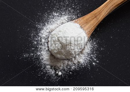 Baking Soda On A Wooden Spoon On Dark Background
