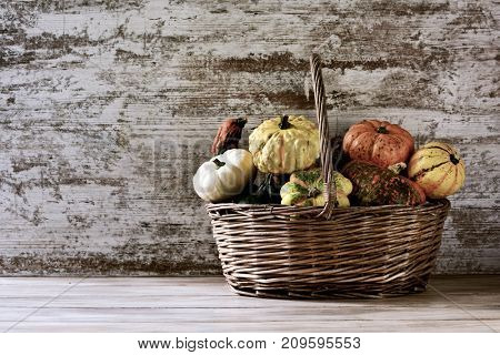 a worn wicker basket with an assortment of different pumpkins against a rustic wooden surface with a blank space on the left