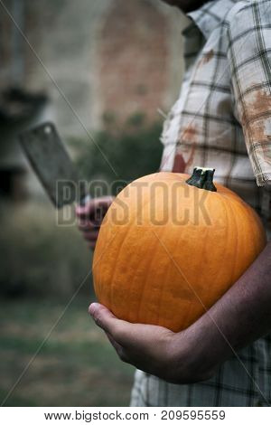 closeup of a scary man wearing dirty and ragged clothes with a pumpkin in one hand and a rusty and bloody cleaver in the other hand in front of a house in ruins