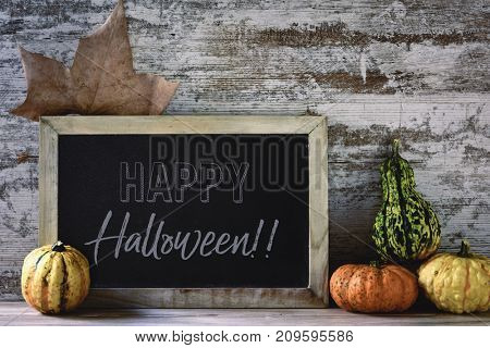 a wooden-framed chalkboard with the text happy halloween, an autumn leaf and some different pumpkins on a rustic wooden table