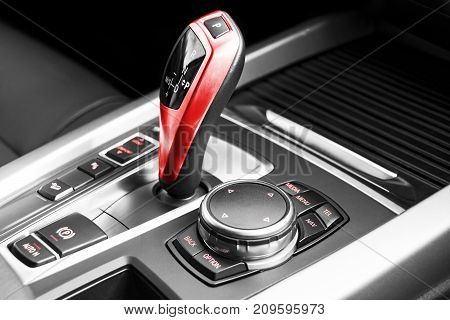 Red Automatic gear stick of a modern car car interior details. Black and white