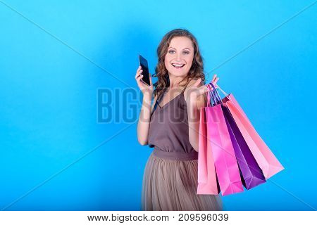 Happy young smiling woman in dress holding shopping bags and mobile smart phone over blue background in black friday holiday free space. Beauty fashion seasonal sale concept copy space