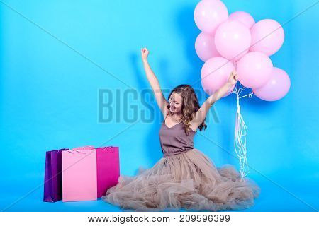 Beautiful young woman sitting with hands up near shopping bags and pink balloons over blue background in black friday holiday free space. Beauty fashion seasonal sale concept copy space