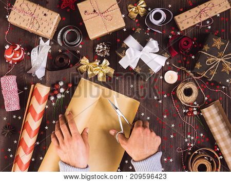 Man hand holding roll of kraft wrapping paper with scissors for cutting packing christmas gift box. Process of package new year gift box. Christmas packaging wrapping paper ribbon twine bow and thread scissors balls on wooden background.