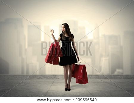 A stylish female standing with red shopping bags on platform and city view landscape backround concept