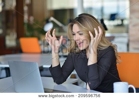 Frustrated angry woman screaming on her laptop