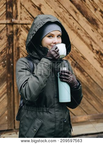 Young woman with cup of hot herbal tea and thermos flask outdoors