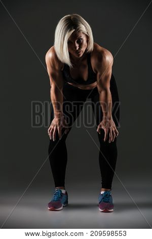 Full length portrait of a tired female sportswoman standing and resting isolated over gray background
