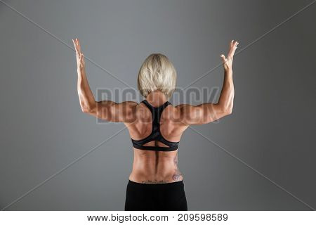 Back view portrait of a muscular strong sportswoman showing her muscles while standing isolated over gray background