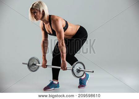 Full length portrait of a muscular adult sportswoman holding heavy barbell isolated over gray background