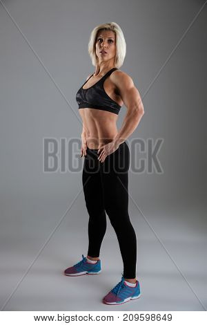 Full length portrait of a motivated muscular adult sportswoman standing with arms on hips and looking at camera isolated over gray background