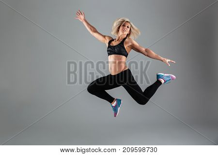 Full length portrait of a smiling muscular adult woman jumping isolated over gray background