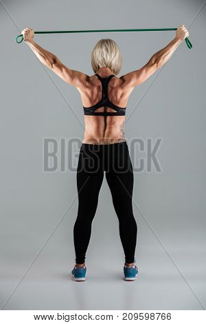 Full length back view portrait of a muscular adult sportswoman working out with a stretching band isolated over gray background