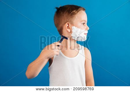 Young boy trying shaving his face like man and looking aside over blue background