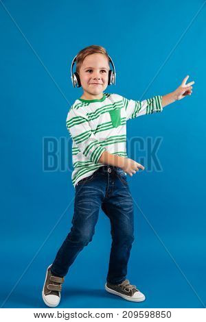 Full length image of cheerful young boy listening music and dancing over blue background
