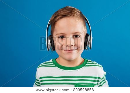 Close up portrait of smiling young boy listening music by earphone and looking at the camera over blue background