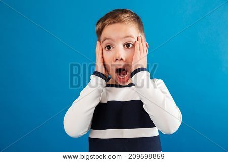 Shocked young boy in sweater holding head and looking away over blue background