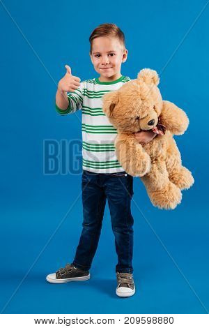 Full length portrait of a happy little boy holding teddy bear and showing thumbs up gesture isolated over blue background
