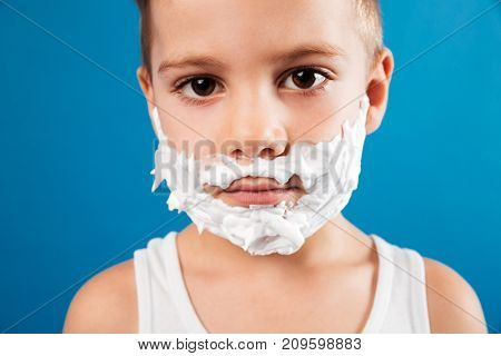 Close up portrait of calm young boy in shaving foam like man looking at the camera over blue background