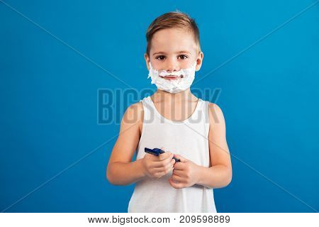 Smiling young boy in shaving foam holding razor like man and looking at the camera over blue background