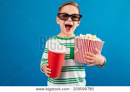 Happy young boy in eyeglasses preparing to watch the film while holding soda and popcorn over blue background