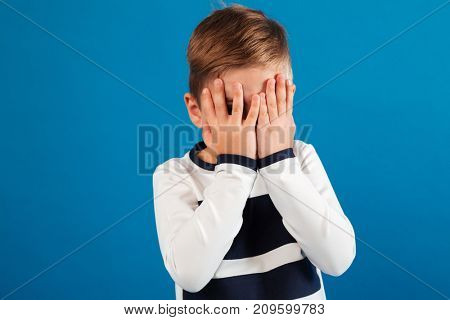 Picture of Young boy in sweater covering his face over blue background