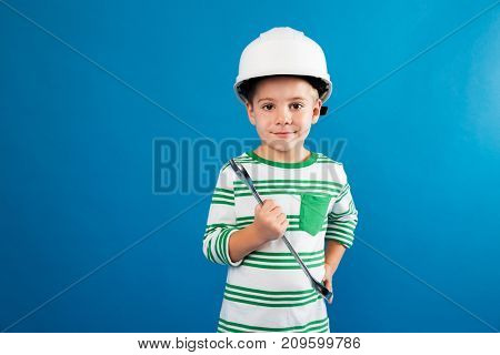 Pleased young boy in protective helmet posing with wrench like engineer and looking at the camera over blue background