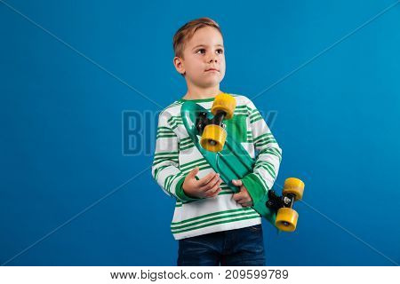 Picture of Young boy holding skateboard and looking aside over blue background