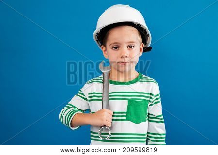 Young boy in protective helmet posing with wrench like engineer and looking at the camera over blue background