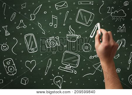 A person drawing media and communication icons on school blackboard with chalk