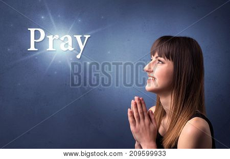 Young woman praying on a blue background with the word Pray written above her