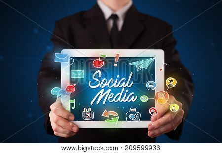 Businessman holding tablet with social media icons