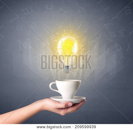 Young female hand holding coffee cup with a lightbulb and alphabet letters above it