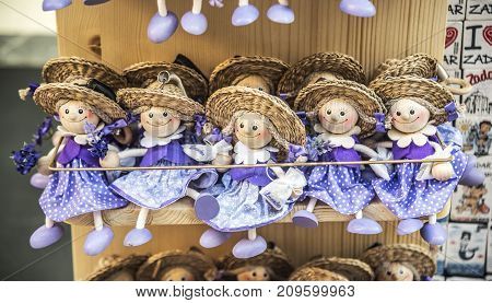 ZADAR, CROATIA - JULY 14, 2017: Wooden dolls dressed in purple outfits, souvenir from Croatia