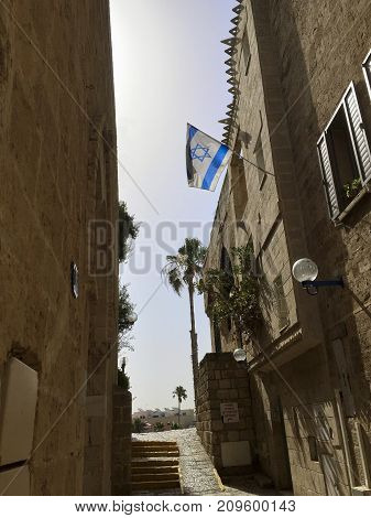 Historic old city of Jaffa a part of the city of TelAviv in Israel. A Flag of Israel blowing in the wind