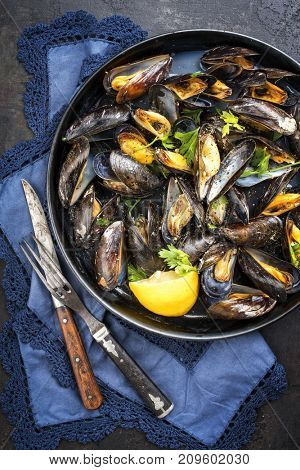 Traditional barbecue Italian blue mussel in white wine as top view in a casserole