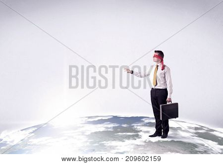 Young blindfolded businessman steps on a realistic globe
