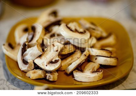 sliced raw champignon Agaricus mushrooms on a yellow plate