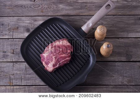Top view of raw beef steak on grill pan. Receipt concept.