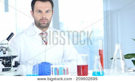 Serious Scientist Sitting In Chemical Laboratory, Microscope