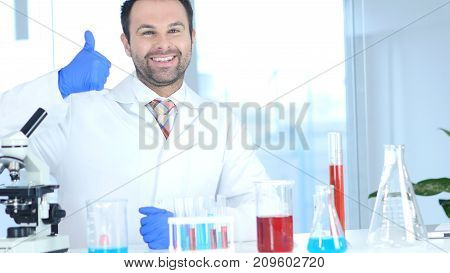Thumbs Up By Positive Scientist In Laboratory
